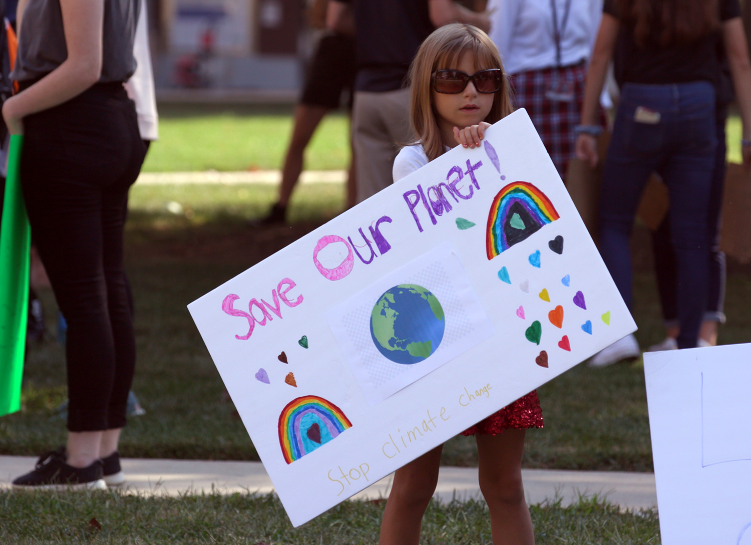 "This is a photo of a child holding a sign with the message, ""Save our planet."""