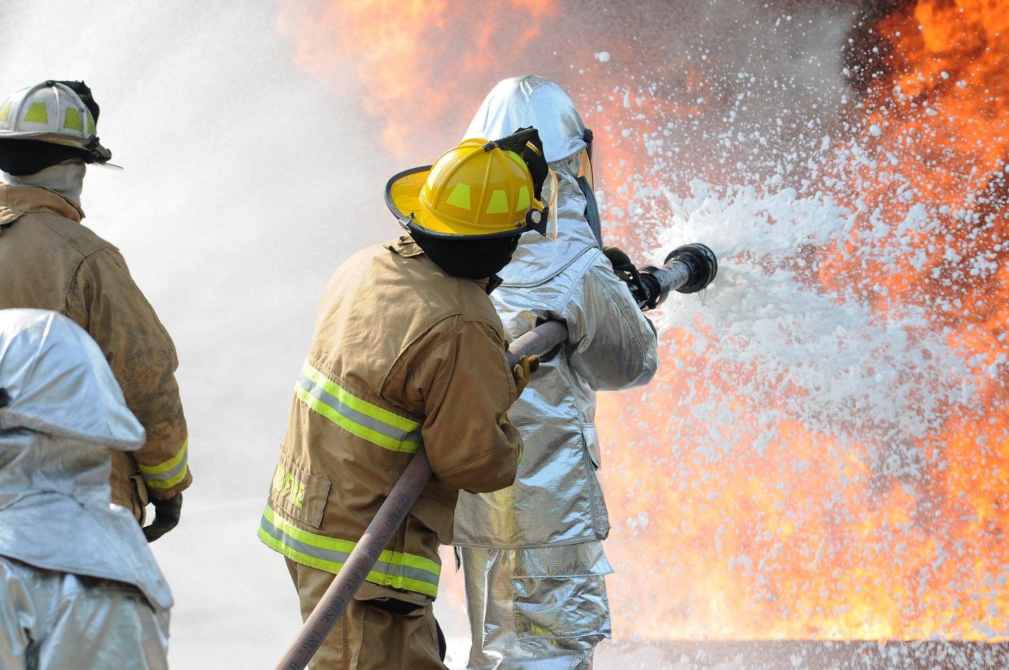Firefighters spraying foam